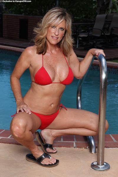 Older blonde woman Jodi West releasing big natural boobs from bikini in pool