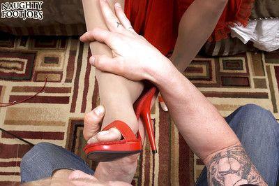 Older brunette lady Christina Cross removing high heels to give footjob
