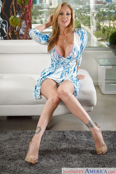 Experienced blonde enchantress Julia Ann playfully strips on a couch