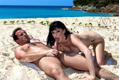 Tattooed MILF pornstar Sofia Valentine giving BJ on beach before doggy sex