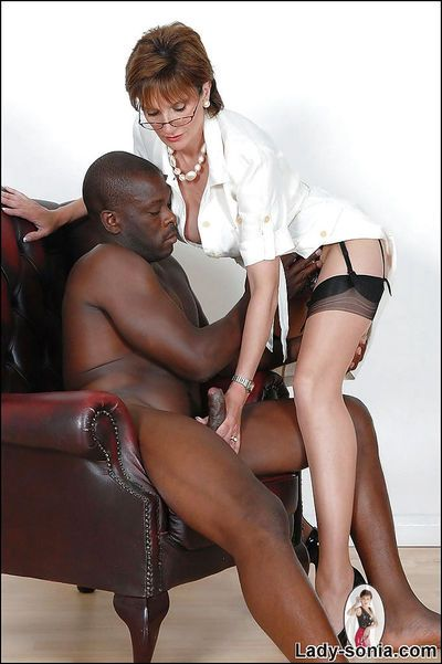 Bosomy mature slut in stockings jerking off a black prick