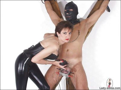 Mature femdom in latex suit torturing her male pets swollen cock