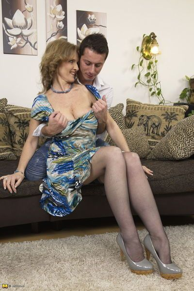 Horny grandmother and her boy toy get busy on chesterfield
