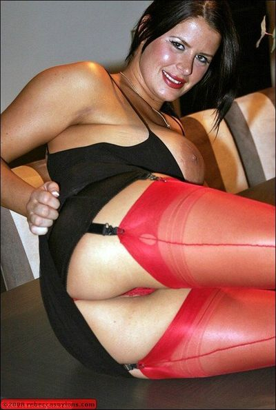 Mature fatty in red nylon stockings posing topless on high heels