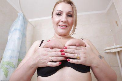 Close up undressing of an mature fatty Dana Karnevali in a bath