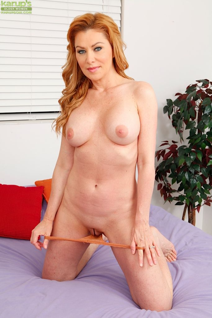 Older redhead Sasha Sean parts shaved vagina and licks own pussy juice