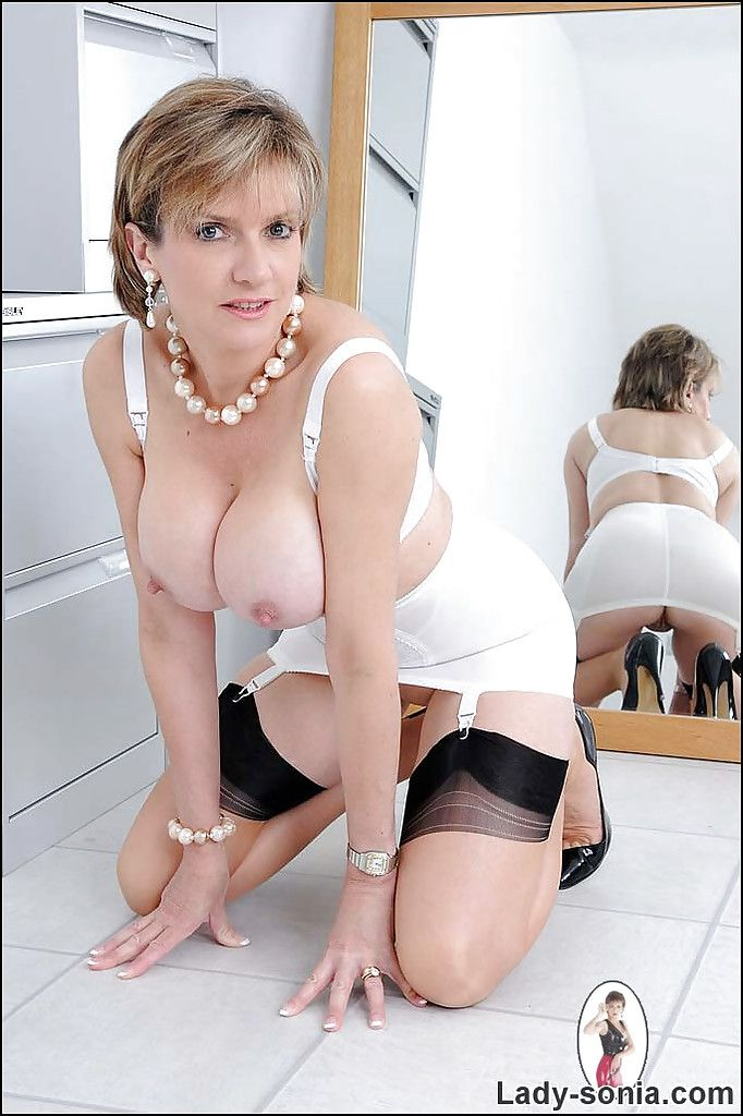 Stunning mature lady on high heels uncovering her big jugs