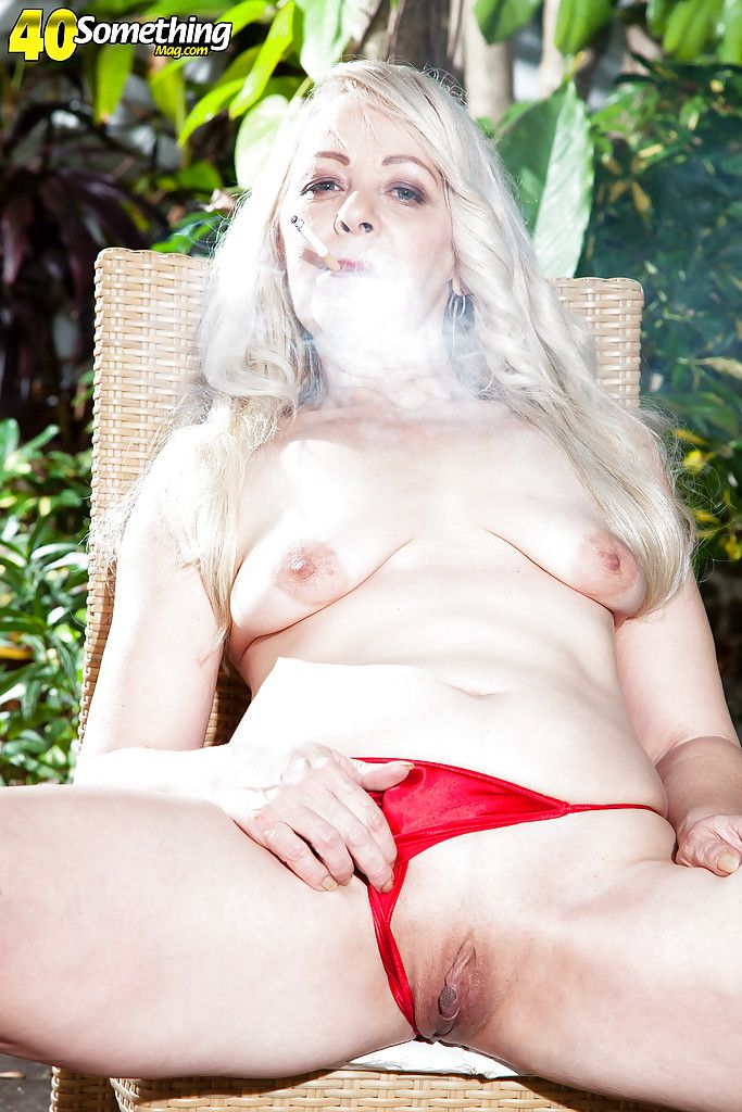 Mature blonde reveals small tits outdoors while smoking a cigarette