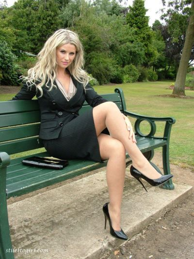 Clothed blonde secretary shows off her legs and pumps in a public park