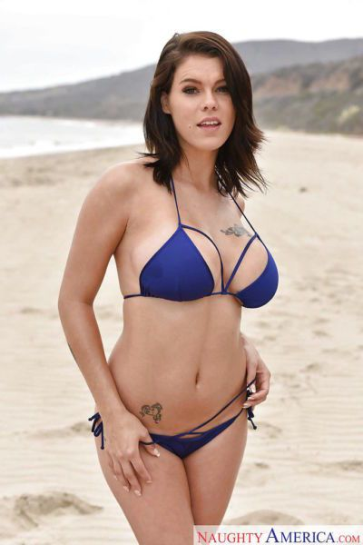 Busty female with amazing curves Peta Jensen posing nude by the beach
