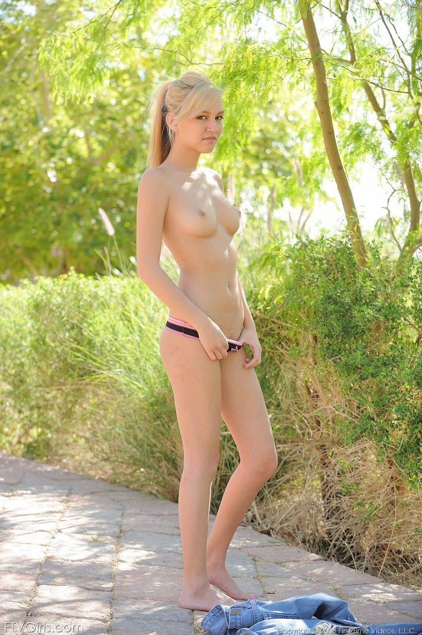 Thin blonde teen removes her blue jeans and underwear on path in garden