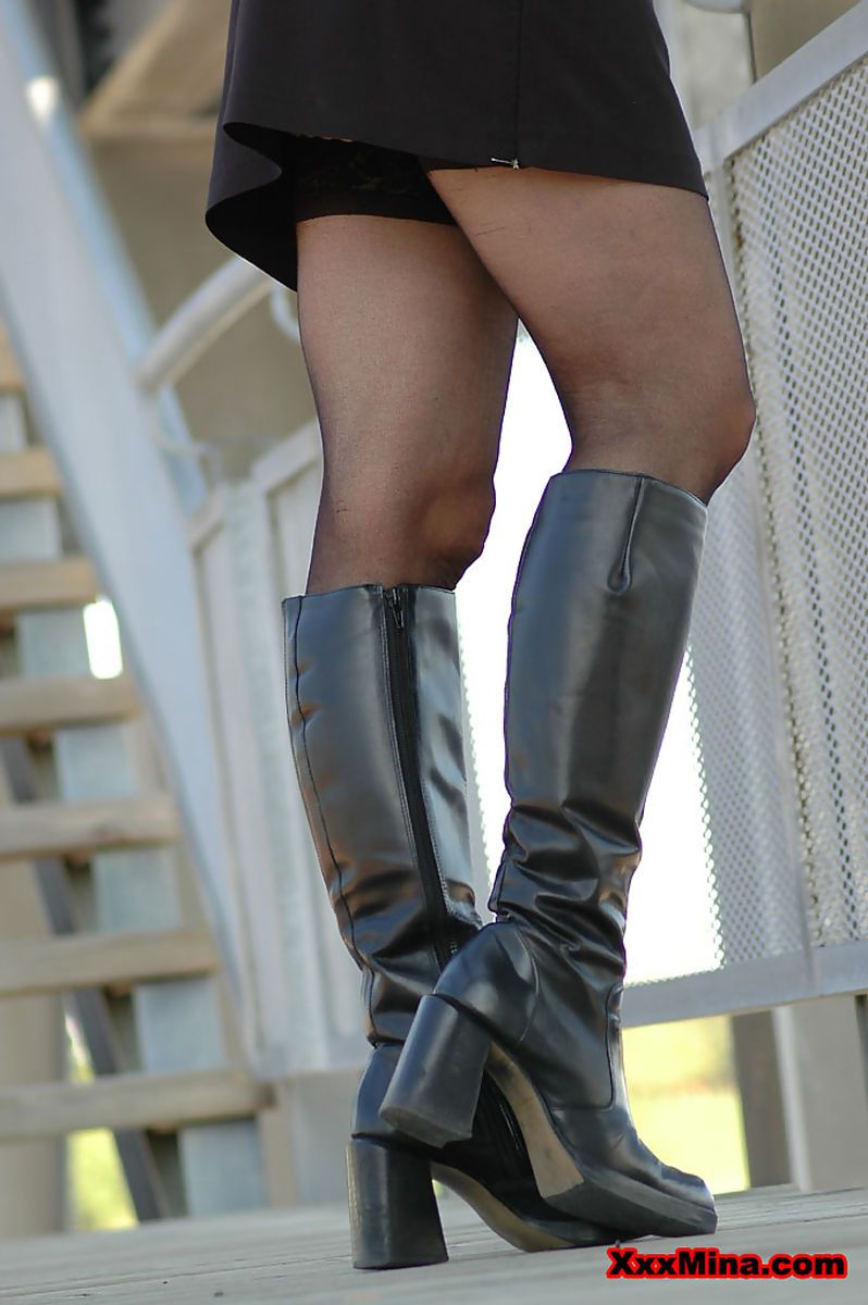 Black clad MILF in boots teases with naked upskirt on outdoor steps