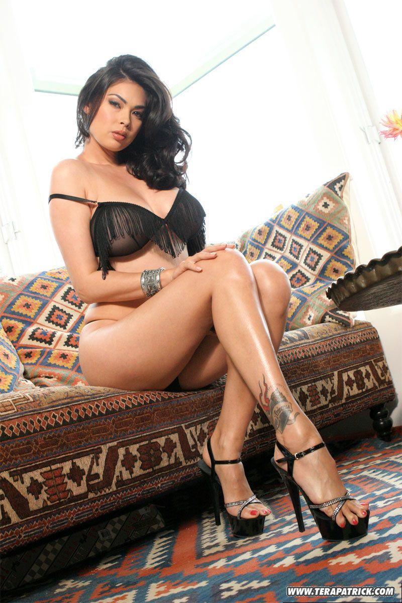 Brunette Asian MILF pornstar Tera Patrick shows big tits in sheer lingerie