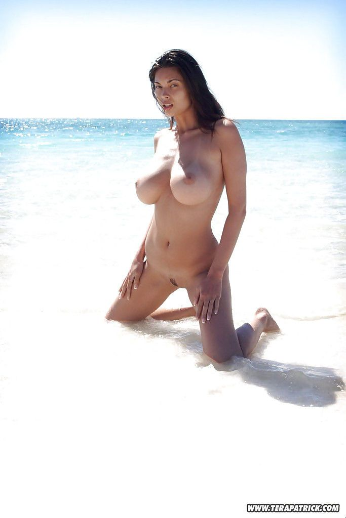 Big busted brunette vixen stripping off her pink panties on the beach
