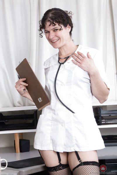 Mature brunette Sunshine shedding doctor garb before exposing hairy twat