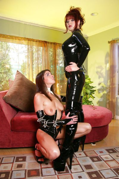 Mature domme in latex outfit and boots whips lesbian lover in BDSM sex game