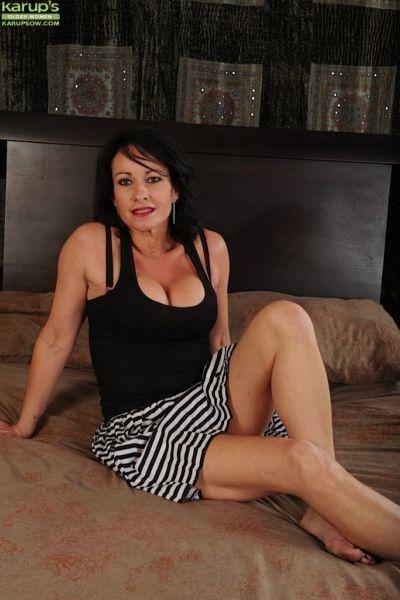 Buxom older lady Braxton Kai exposing large boobs and spreading bald vagina