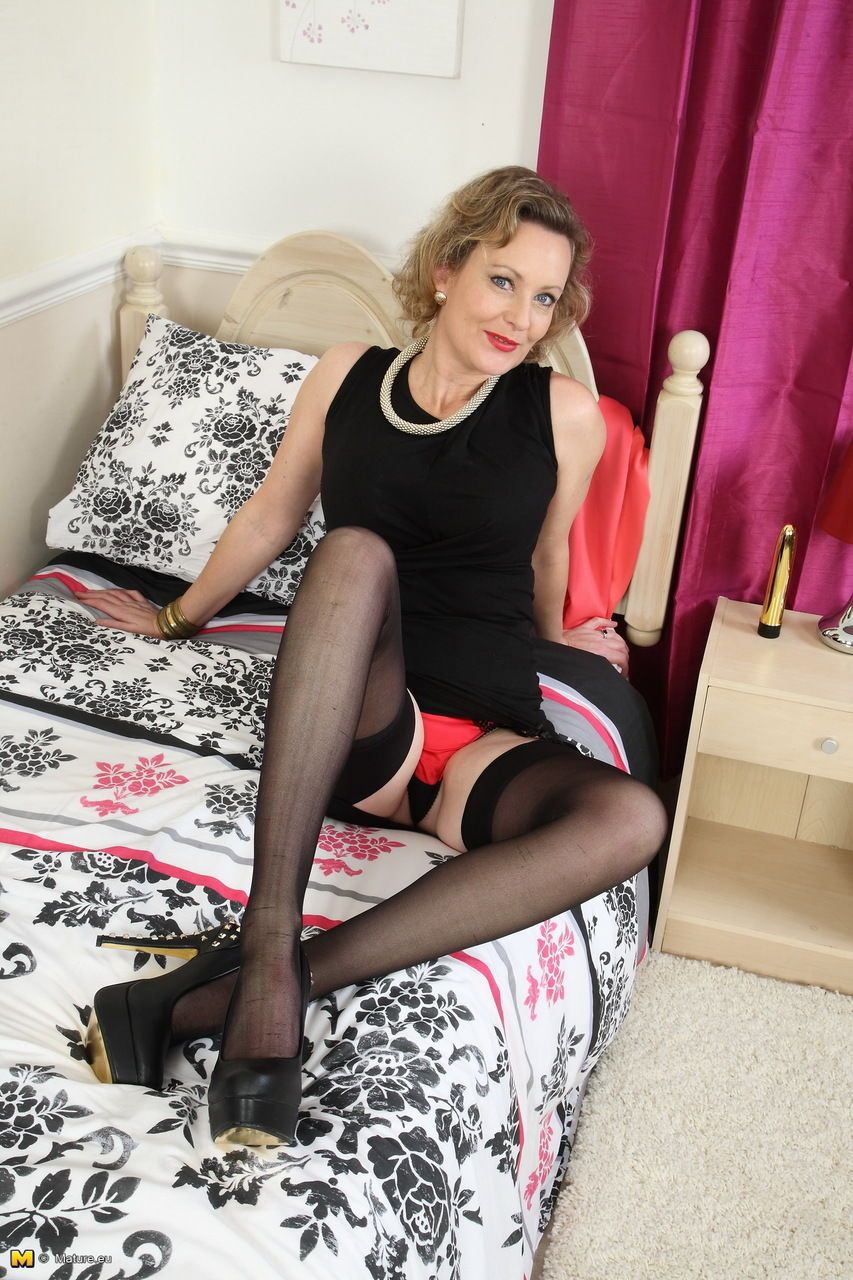 Middle-aged European housewife teases on sofa in stockings and garters