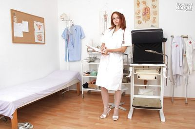 Lusty redhead nurse in nylons undressing and playing with medical tools