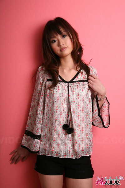 Japanese model with a pretty face stands clothed against a pink wall