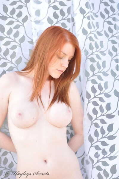 Pale redhead Fi Stevens poses stark naked to show off her beautiful big boobs