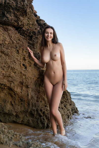 Solo girl Alisa I wanders a sandy shoreline while showing her beautiful body