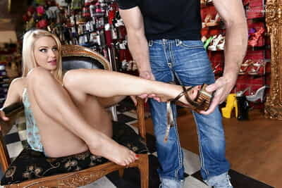 Sexy blonde with great legs has bare feet attended to by shoe salesman