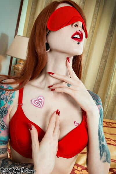 Tattooed redhead Razor Candi toys her asshole in red stockings