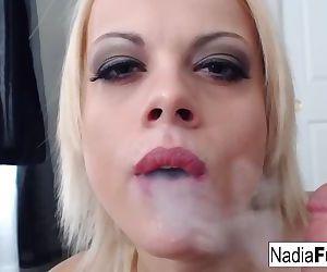 Nadia smokes an e-cig while also..