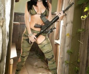 Hot brunette Sophie Dee poses with an automatic rifle..