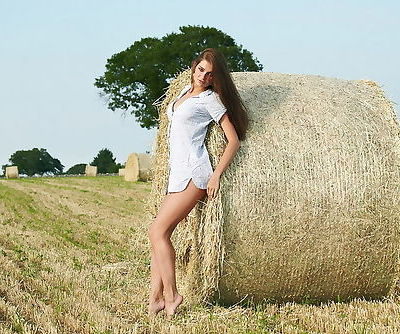Farm girl stands naked with the bales of hay outdoors in her erotic set